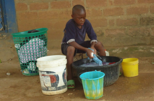 Pictured: the Nigerian boy who does chores when he wants to be in school