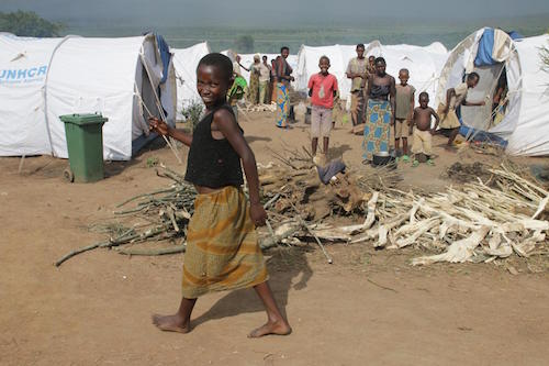 A girl walks past firewood at the Mahama refugee camp Picture: UNICEF/Pflanz