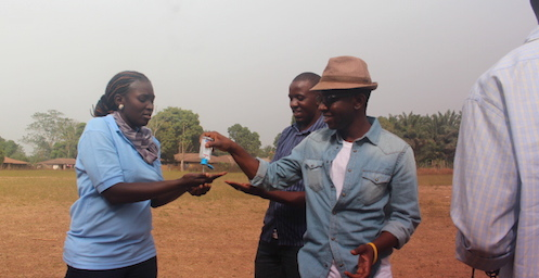 Chernor Bah sanitises his hands during visit to Sierra Leone
