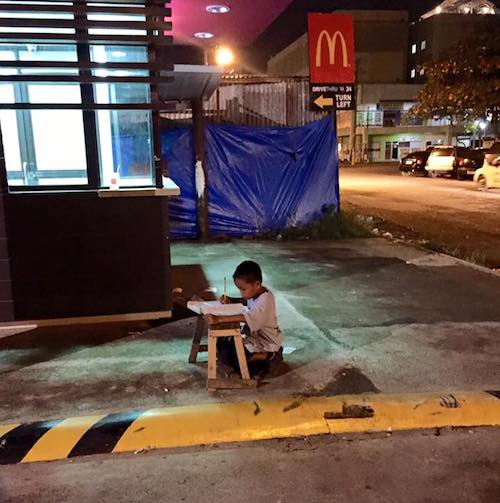 Homeless Philippines boy Daniel Cabrera aged nine does homework by light from McDonald's