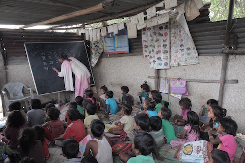 Indian rag picking children at  makeshift classroom inside the slum where they live and work