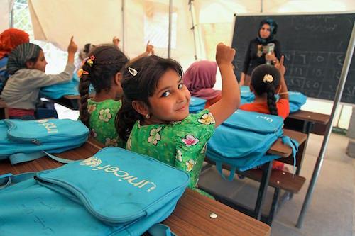 a student raises her hand to answer a question from her teacher Hiba Ahmed in a tent classroom at the Al-Takya Al-Kaznazaniya school in Al-Takya Al-Kaznazaniya IDP camp, near Baghdad. Picture UNICEF/KHUZAIE
