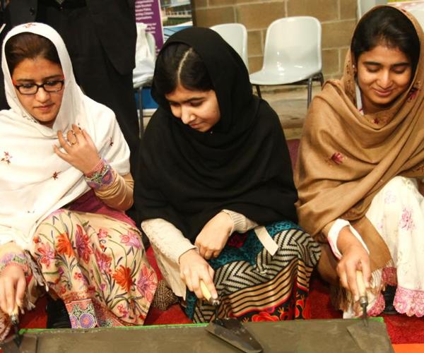 Kainat, Malala and Shazia prepare a brick for the new Burntisland Primary School in Fife