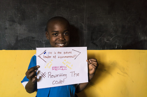 Kenyan schoolgirl in Kibera with #RewritingTheCode poster picture by Theirworld/Adriane Ohanesian