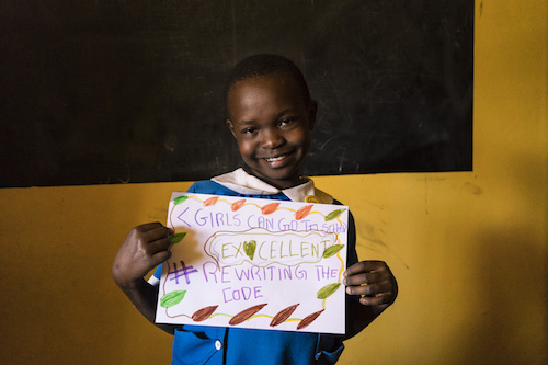 Kenyan schoolgirl in Kibera with #RewritingTheCode poster Theirworld:Adriane Ohanesian