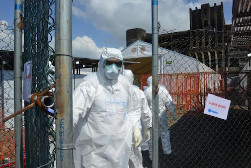 A health worker closes the gate at an Ebola treatment centre in Liberia Picture: UNICEF/Nesbitt