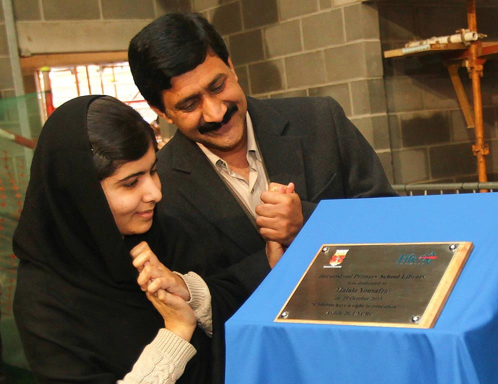 Malala and Ziauddin with the plaque dedicating the new library to her