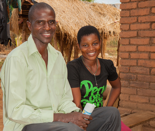 Malawi child marriage - Salome with Benson from her mother and father group picture by Tearfund/Chris Hoskins