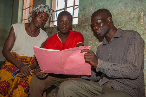 Malawi child marriage - mother and father group checking school attendance register picture by Tearfund/Chris Hoskins