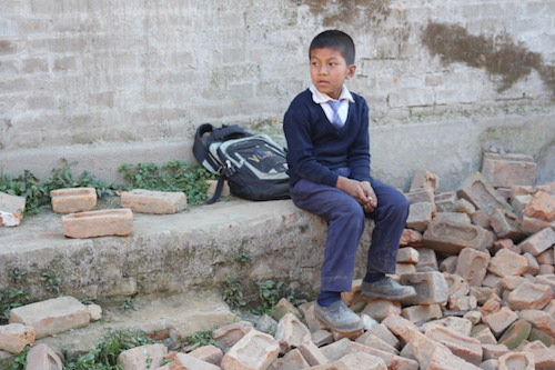 Nepalese boy sits in rubble picture by Claire Wilkinson