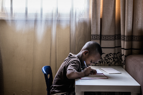 Four-year-old Oluwabukunmi Falayi writes at his desk at home in Abuja, Nigeria Picture: UNICEF/Gilbertson VII