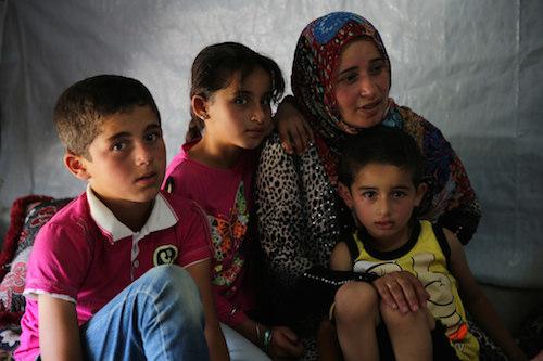 Syrian refugee family at tented settlement in Lebanon