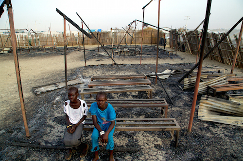 Children sit in the burned ruins of school in Malaka, South Sudan, that was destroyed in fighting in February Picture: UNICEF/George