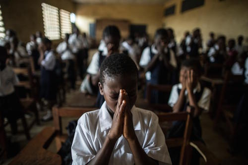 Students pray during a class at Monrovia Demonstration School in the Liberian capital in 2015 Picture: UNICEF/Grile