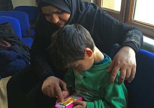 Syrian refugee Mohammed plays a game on a mobile phone with his mother Manal picture by Facebook/Norad
