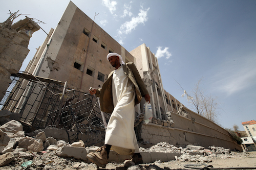 Yemeni guard walks past bombed school in Sana'a picture UNICEF